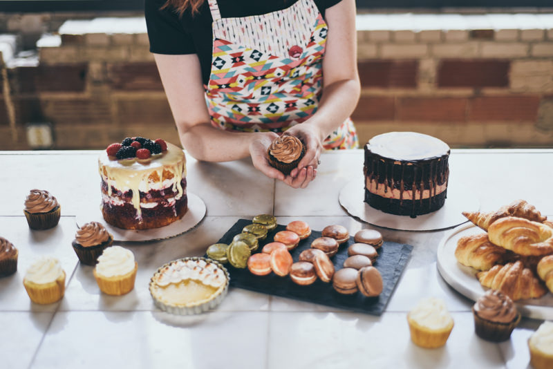 pastry chef holding cupcake above an assortment of pastries