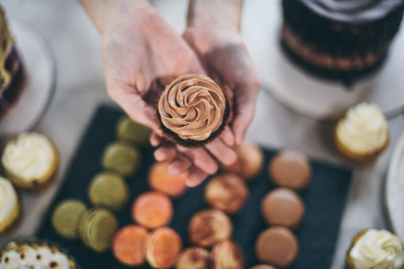 pastry chef holding out a cupcake above many flavors of macarons