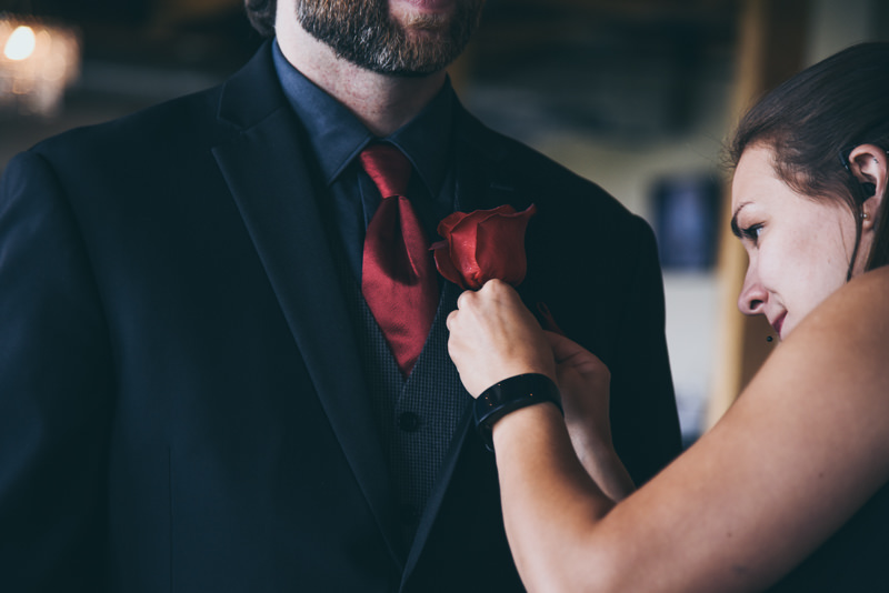 groom getting his boutonniere pinned on