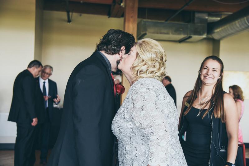 mom kissing groom on the cheek