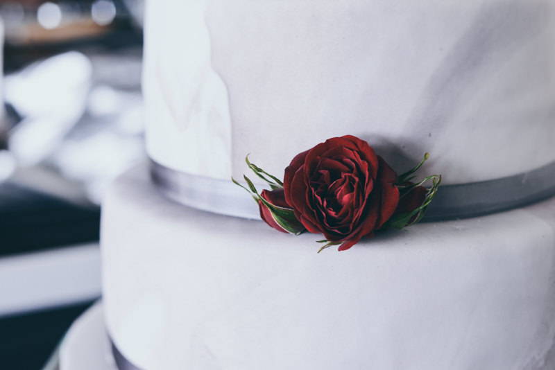 close up of an elegant white cake with a fresh red rose