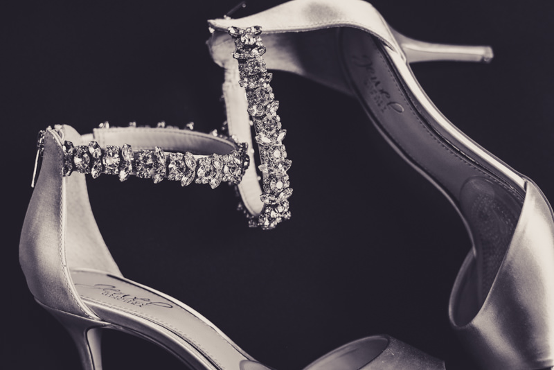 black and white image of a brides heels with rhinestones