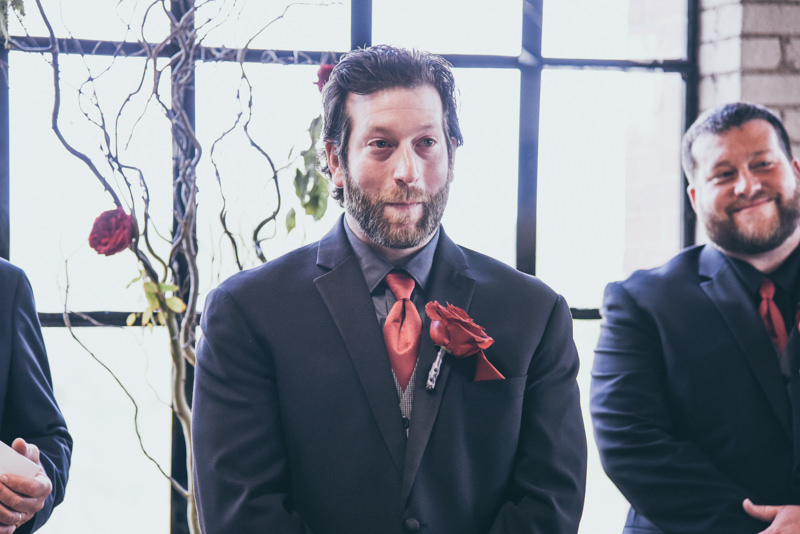 grooms face as he sees his bride come down the aisle