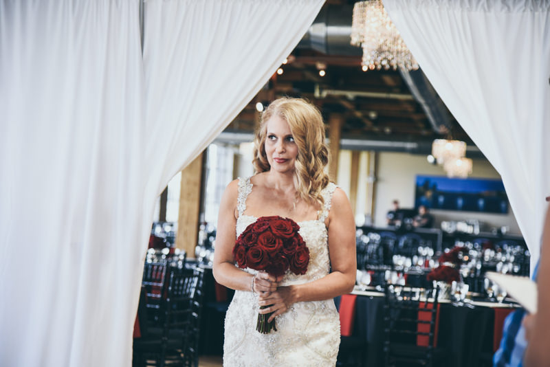 bride walking between white curtains to go down the aisle