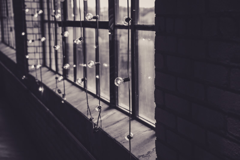 black and white image of bistro lights in a large window