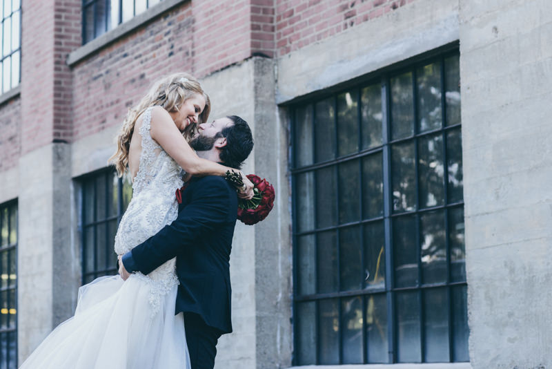 groom picking up his bride and looking into her eyes in front of an old building