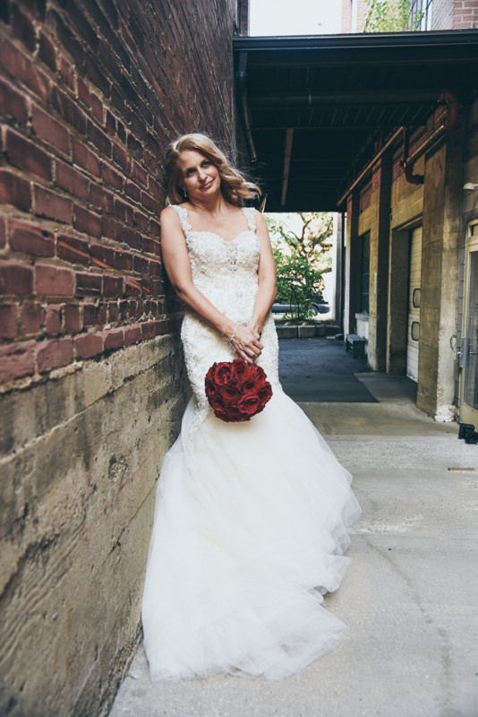 a bride with a red bouquet in an brick alley