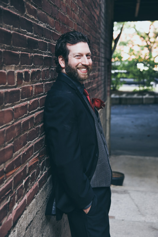 a groom in a black tux, gray vest, with a red boutonniere, in a brick alley