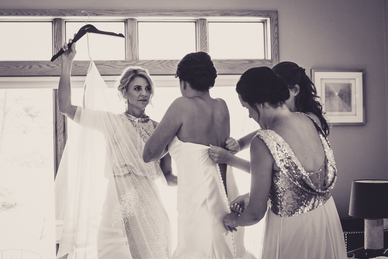 bridesmaids getting bride into dress