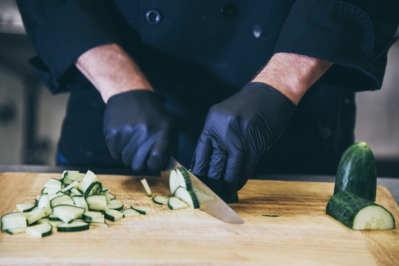 close up of a caterers hands prepping food