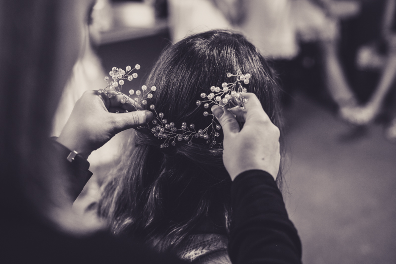 bride getting a hairpiece put in before wedding