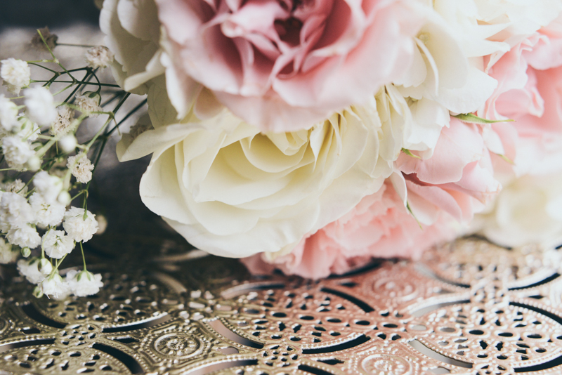 close up of wedding bouquet against gold filigree cart