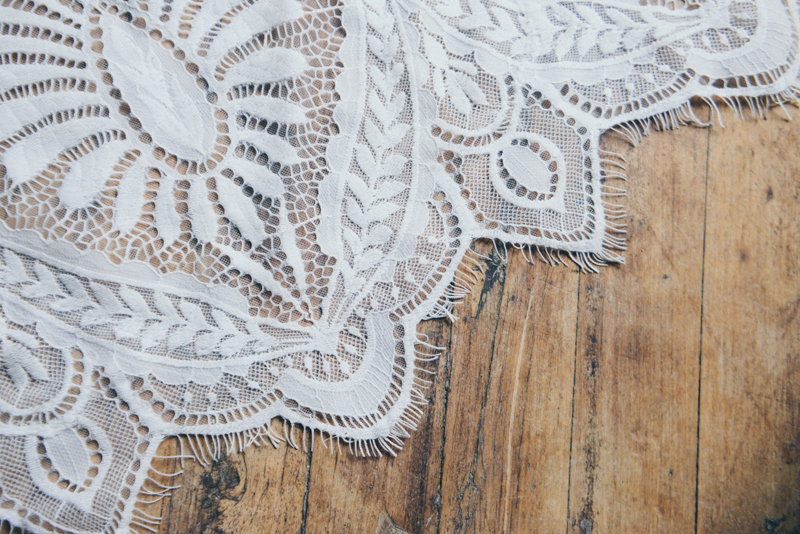 lace detail of a wedding gown on a wooden floor